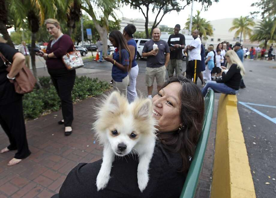 A queue and a cutie:Voters had to wait in a long line at the Gwen Margolis Community Center in North Miami, but at least Elsa Khan had Timberland to keep her company. Photo: Walter Michot, Associated Press