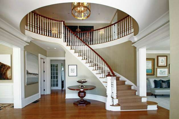 The home's recurring theme of circles and ovals can be clearly seen in the opening for the staircase upon walking into the home's foyer. Photo: Contributed Photo