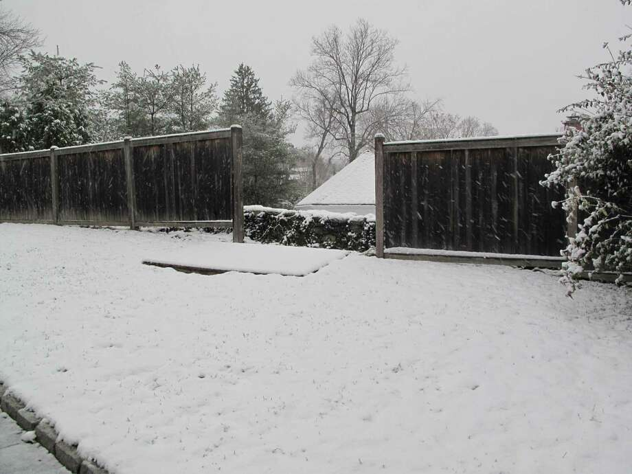 A fence broken by Hurricane Sandy now rests in snow on Kimberly Place in New Canaan, Conn. Nov. 7, 2012. Photo: Tyler Woods