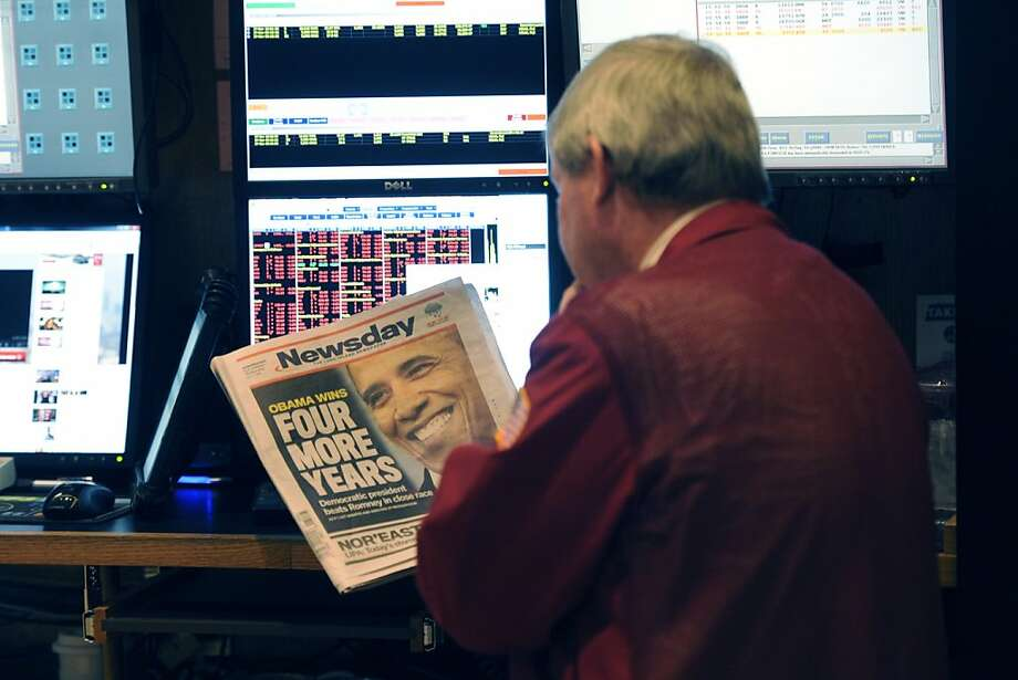 """A trader on the floor of the New York Stock Exchange looks at the front page of a newspaper the day after Pres. Barack Obama was re-elected, Wednesday, Nov. 7, 2012 in New York. With President Barack Obama elected to another term, U.S. investors dumped stocks Wednesday and turned their focus to a world of problems, including a """"fiscal cliff"""" of tax increases and spending cuts at home and a deepening recession in Europe. (AP Photo/Henny Ray Abrams) Photo: Henny Ray Abrams, Associated Press"""