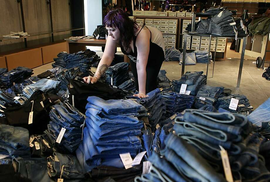 Chelsea Guerra organizes stacks of blue jeans in the Diesel outlet store at the Paragon mall in Livermore. Photo: Paul Chinn, The Chronicle