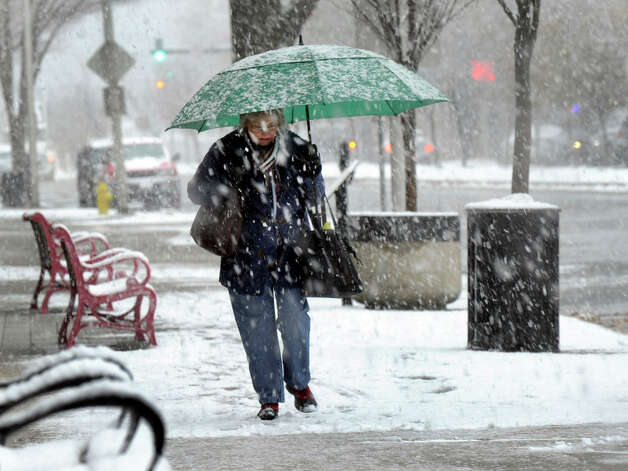 A woman walks in the snow on Main Street in Danbury Wednesday afternoon, Nov. 8, 2012. Photo: Carol Kaliff / The News-Times