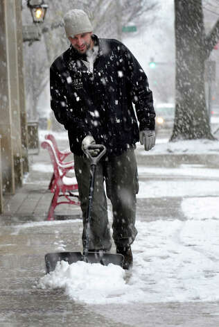 Erik Carr, of Bethel, working for CityCenter Danbury, shovels the sidewalk on Main Street Wednesday during the afternoon snowfall, Nov. 7, 2012. Photo: Carol Kaliff / The News-Times