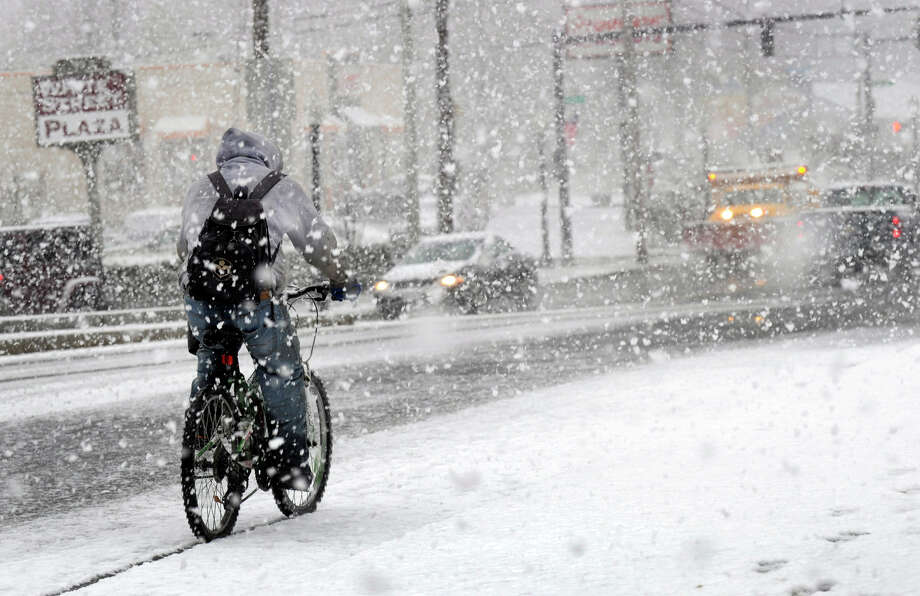 A bicyclist rides in the snow down White Street in Danbury Wednesday afternoon, Nov. 7, 2012. Photo: Carol Kaliff / The News-Times
