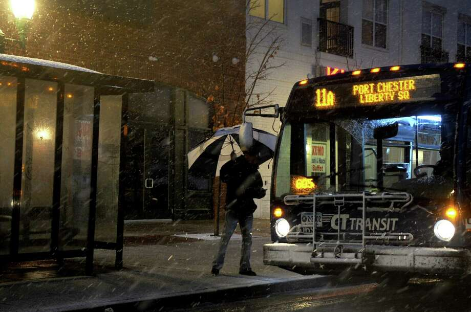 A pedestrian boards a bus on East Main Street in Stamford as heavy snow falls from a nor'easter on Wednesday, November 7, 2012. Photo: Lindsay Niegelberg / Stamford Advocate