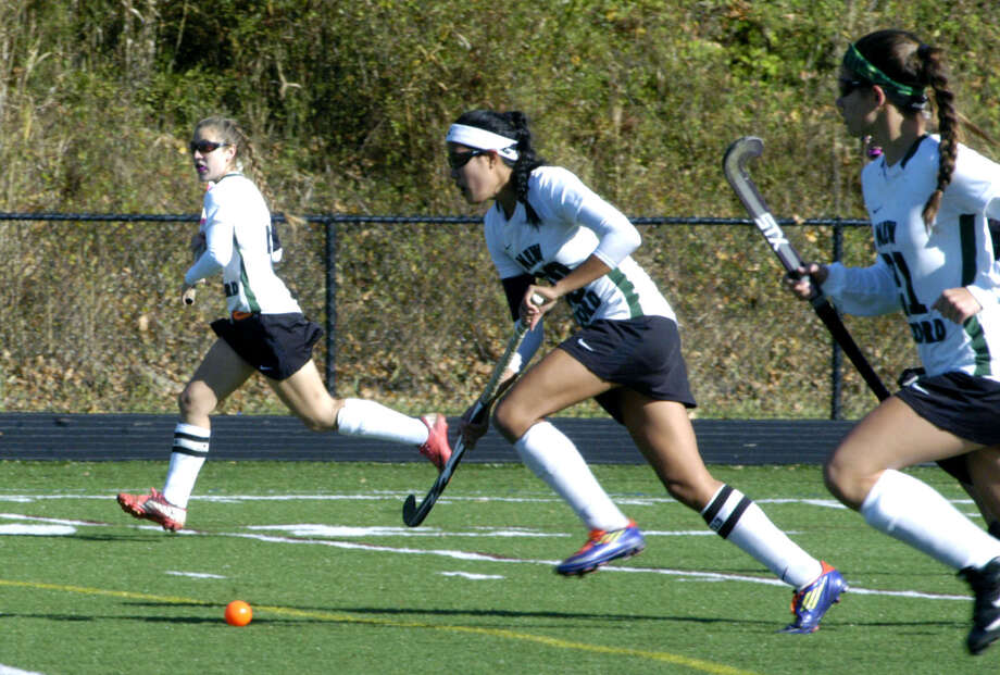 Kristi Montemurro centers a Green Wave rush flanked by Emily Sanders, left, and Cristina Munoz during New Milford High School field hockey's 3-1 victory over Joel Barlow in the South-West Conference playoff semifinals at Immaculate High in Danbury. Nov. 4, 2012 Photo: Norm Cummings