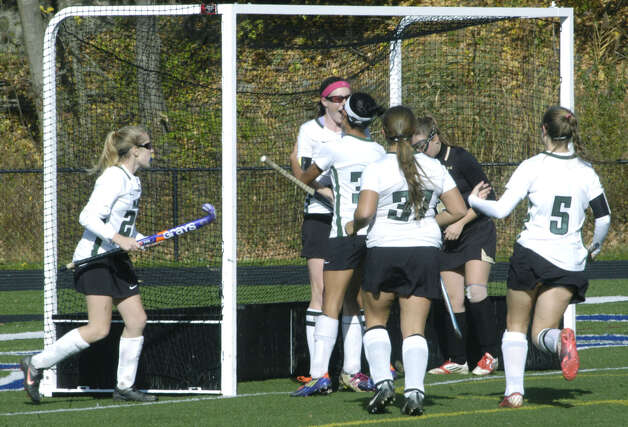 Celebrating the Green Wave's first goal are, from left to right, Taylor Duffany (20), Olivia Monteiro (11), Kristi Montemurro (30), Lindsey Heaton (37) and Emily Sanders (5) during New Milford High School field hockey's 3-1 victory over Joel Barlow in the South-West Conference playoff semifinals at Immaculate High in Danbury. Less enthusiastic about this turn of events is a Falcon defender standing in the far corner of the cage. Nov. 4, 2012 Photo: Norm Cummings