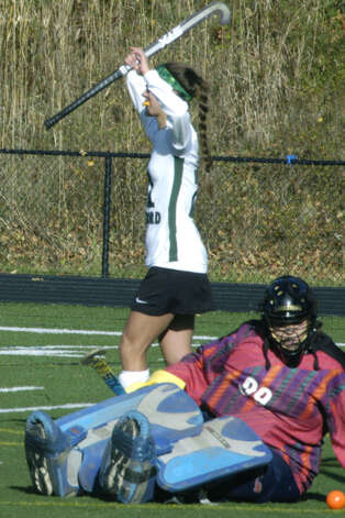 Falcon netminder Sam Scavo can only stare at the ball as Green Wave senior Cristina Munoz celebrates her team's second score during New Milford High School field hockey's 3-1 victory over Joel Barlow in the South-West Conference playoff semifinals at Immaculate High in Danbury. Nov. 4, 2012 Photo: Norm Cummings