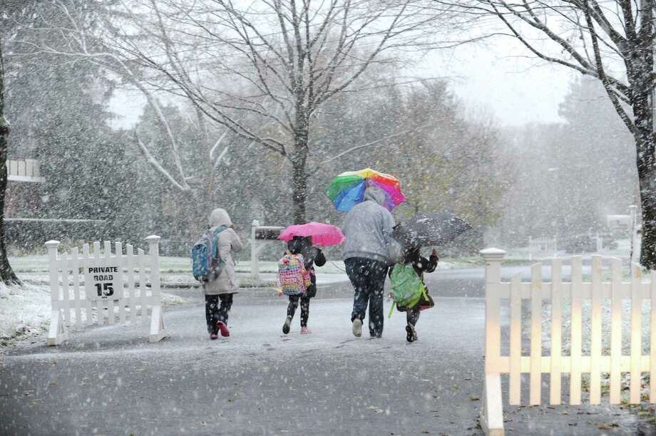 Insley Carpenter, 9, with her sister Ella 7, the babysitter, Jackeline, Da Silvo, and sister Lucy, 5, walk on Sound Beach Avenue from Old Greenwich School in Conn. Wednesday, Nov., 7, 2012, during the Nor'easter. Photo: Helen Neafsey / Greenwich Time
