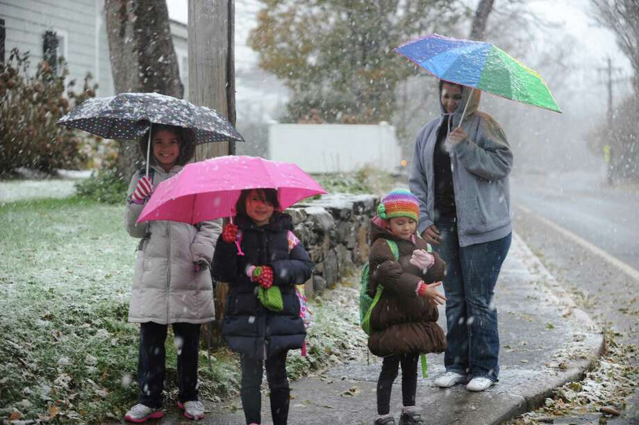 Insley Carpenter, 9, Ella, 7, and Lucy, 5, with babysitter Jakeline DaSilvo walk on Sound Beach Avenue from Old Greenwich School in Conn. Wednesday, Nov., 7, 2012, during the Nor'easter. Photo: Helen Neafsey