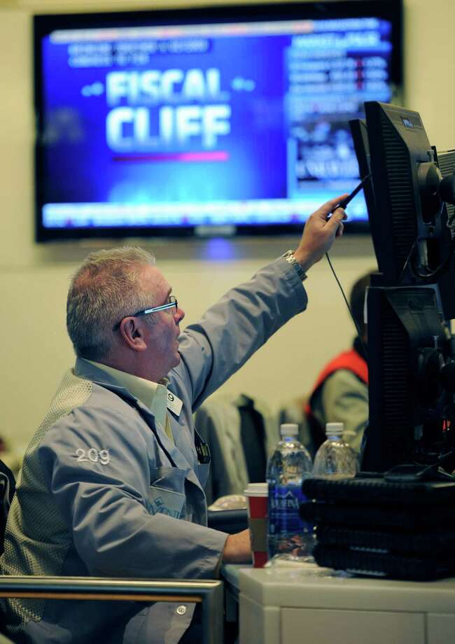 "James Dresch of MND Partners Inc. works on the floor of the New York Stock Exchange the day after Pres. Barack Obama was re-elected, Wednesday, Nov. 7, 2012 in New York. With President Barack Obama elected to another term, U.S. investors dumped stocks Wednesday and turned their focus to a world of problems, including a ""fiscal cliff"" of tax increases and spending cuts at home and a deepening recession in Europe. (AP Photo/Henny Ray Abrams) Photo: Henny Ray Abrams, Associated Press / FR151332"