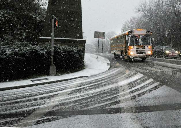 A Greenwich school bus on a snow-covered East Putnam Avenue prepares to make a right onto Laddins Rock Road in Old Greenwich during the nor'easter that hit town, Wednesday, November 7, 2012. Wednesday was the first day back for students in the Greenwich schools that had been closed due to the damage caused by Hurricane Sandy. Photo: Bob Luckey / Greenwich Time