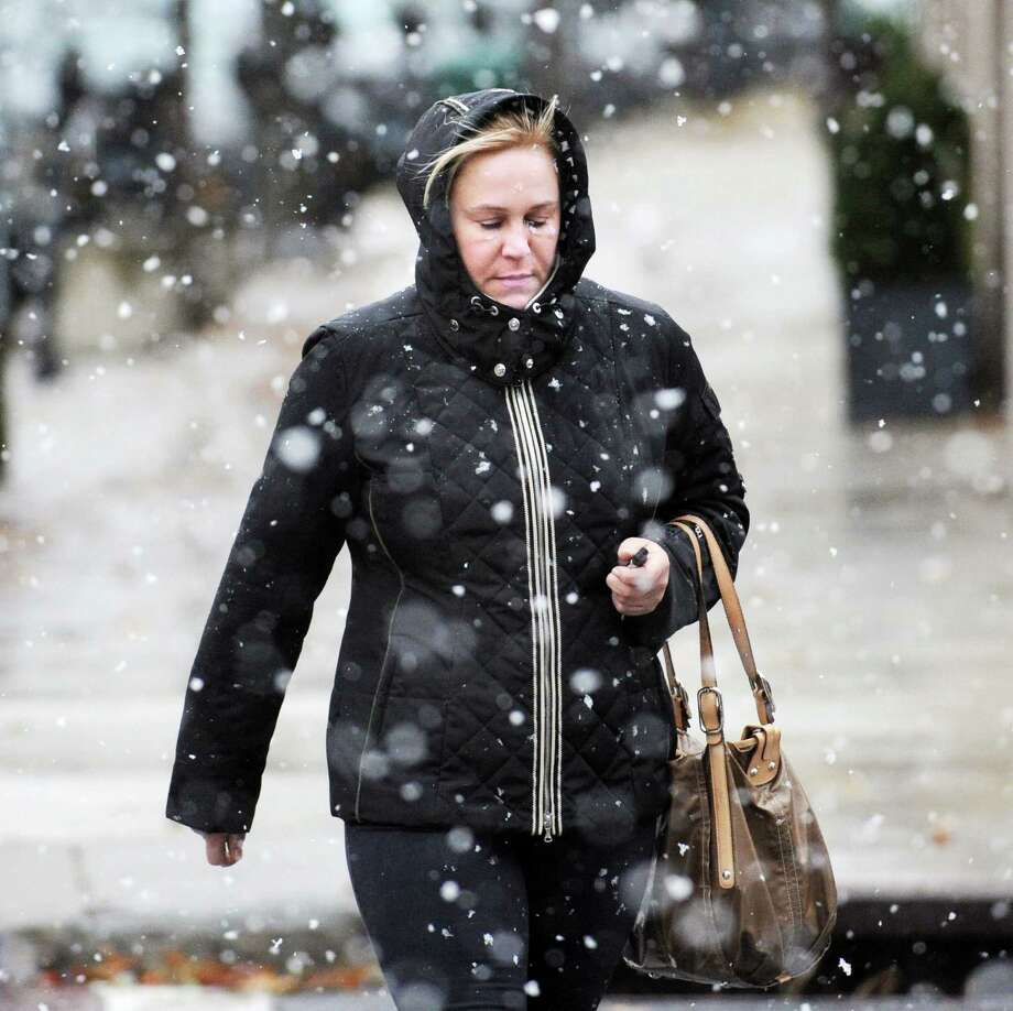 Christina Powers of Greenwich has the hood of her coat up as she walks in the driving snow on Greenwich Avenue during the nor'easter that hit town, Wednesday, November 7, 2012. Photo: Bob Luckey / Greenwich Time