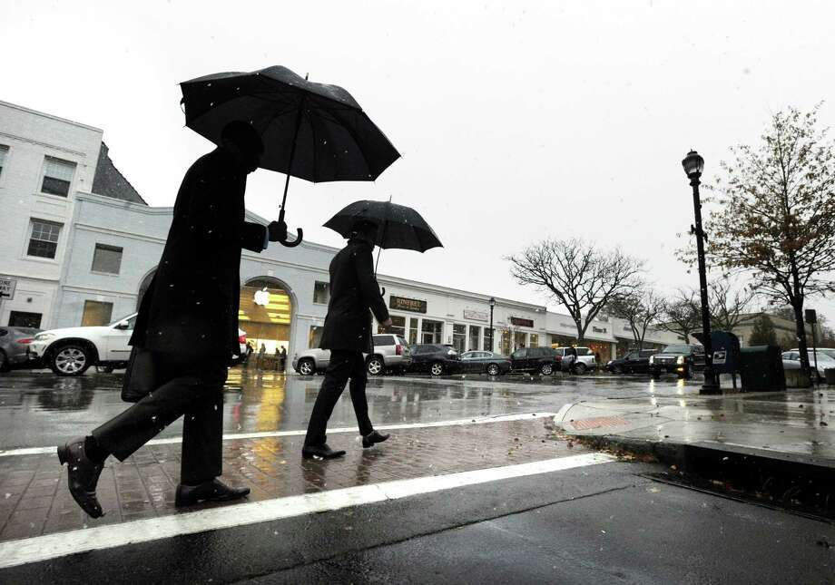 Two men with umbrellas walk on Greenwich Avenue during the nor'easter that hit town, Wednesday, November 7, 2012. Photo: Bob Luckey / Greenwich Time