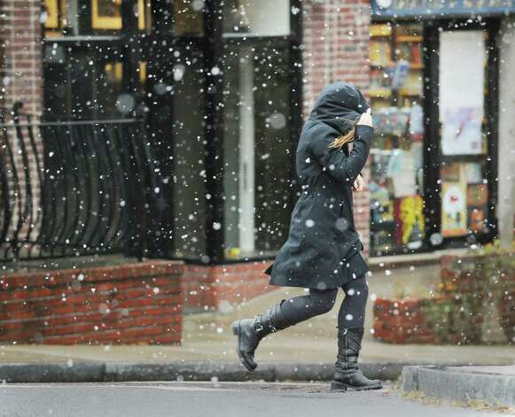 A woman walks on Greenwich Avenue in the snow during the nor'easter that hit town, Wednesday, November 7, 2012. Photo: Bob Luckey / Greenwich Time