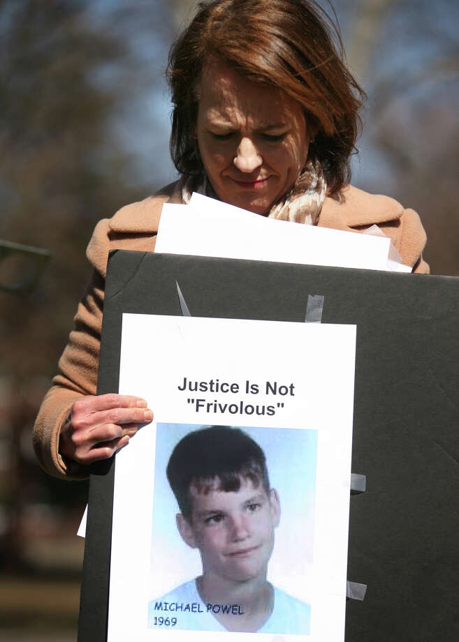 Anne Barrett Doyle, co-director of BishopAccountability.org of Waltham, MA, hold a photo of abuse victim Michael Powel whose family recently settled a civil suit against the Bridgeport Catholic diocese, during a protest at Bridgeport Catholic diocesan headquarters at 238 Jewett Ave. in Bridgeport on Monday, March 28, 2011. Photo: Brian A. Pounds, Brian A. Pounds/file Photo / Connecticut Post
