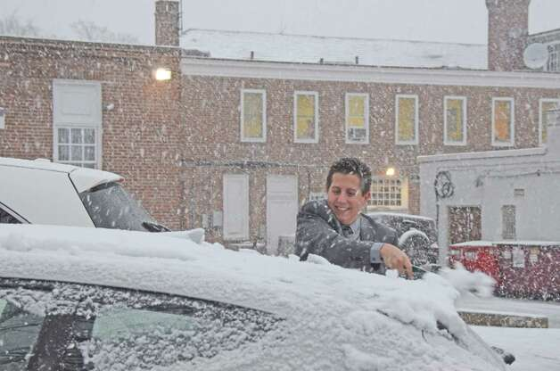 Ryan Mones of Bank of America helps a friend out after work, wiping the snow off her car windows.  Nov. 7, 2012, New Canaan, Conn. Photo: Jeanna Petersen Shepard