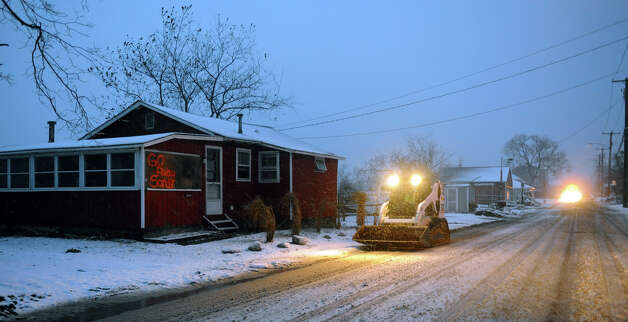 A bobcat operated by Paul Laudine, of Fairfield, makes its way along Fairfield Beach Road in Fairfield, Conn. on Wednesday November 7, 2012. Laudine was using it to put sand dunes back at people's homes after they had been washed away by Hurricane Sandy. Photo: Christian Abraham / Connecticut Post