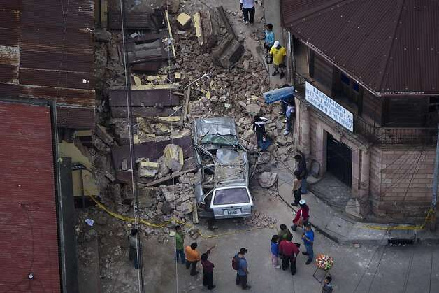 Residents walk among rubble after a 7.4-magnitude earthquake struck in San Marcos, Guatemala. Dozens died, and all but one of Guatemala's 22 states reported damage. Photo: Moises Castillo, Associated Press