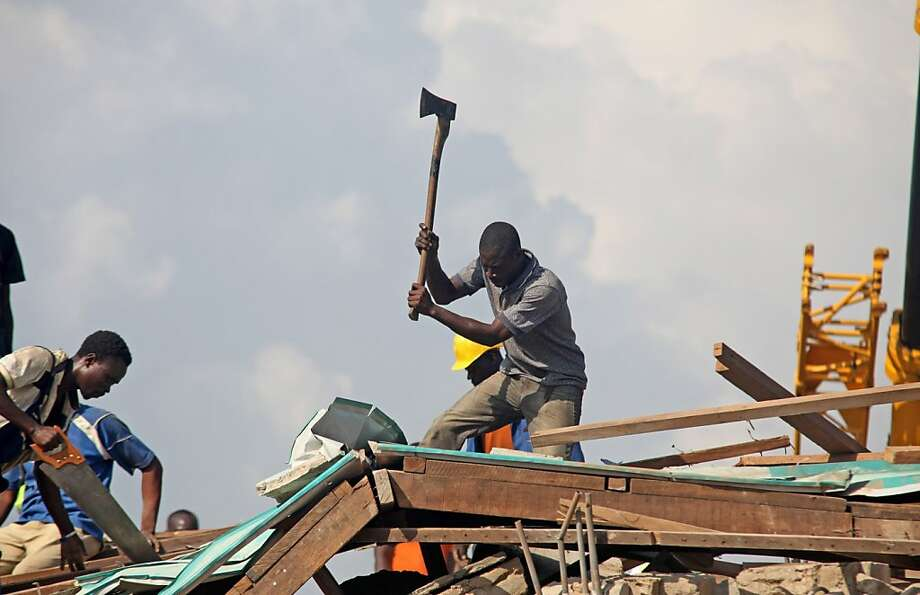 Rescue workers clear rubble from a building as they search for victims of the collapse of a shopping center that was recently built near Accra, Ghana. Dozens of people were hurt and a least one was killed when the five-story structure fell. Photo: Christian Thompson, Associated Press
