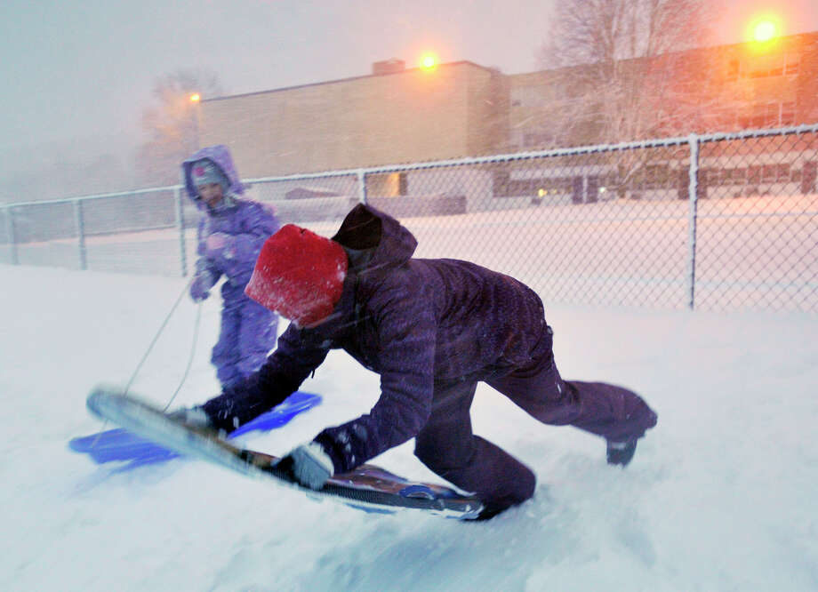 Sophie Rundhaug, 12, foreground, sleds down the hill behind Immaculate High School as her sister, Grace, 7, looks on, as a November nor'easter arrives in Danbury on Wednesday, Nov. 7, 2012. Photo: Jason Rearick / The News-Times