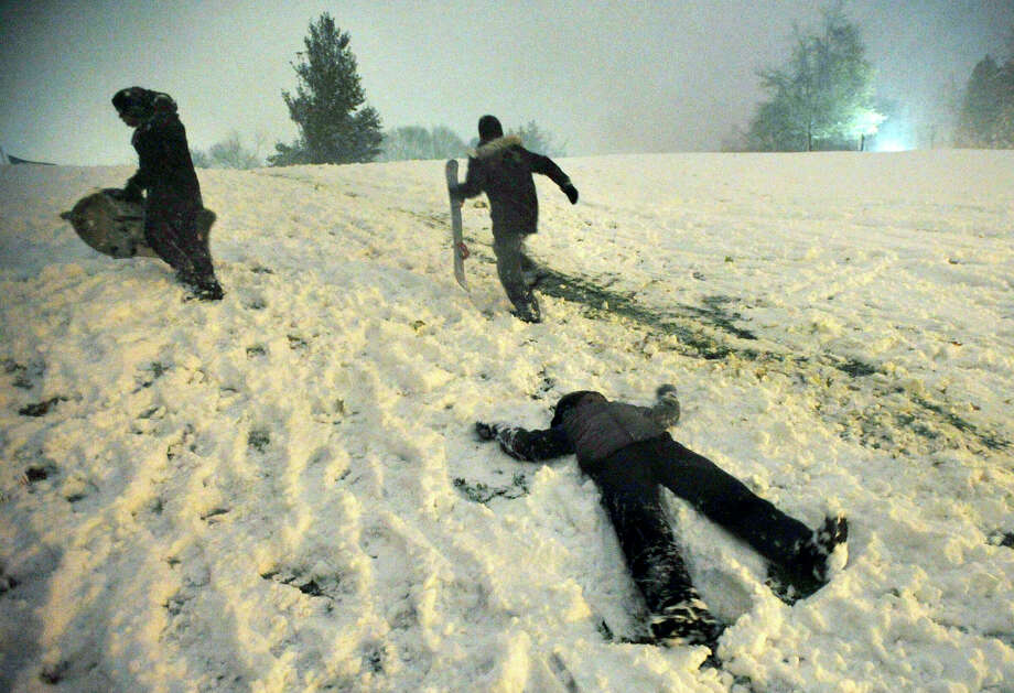 Kai Baldwin, 10, foreground, makes a snow angel, and James Lema, 12, left, and Javen Duff, 11, climb the hill in front of Immaculate High School with their snowboards as the nor'easter arrives in Danbury on Wednesday, Nov. 7, 2012. Photo: Jason Rearick / The News-Times