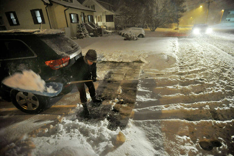 Casey Gage shovels her driveway along Lincoln Avenue as a November nor'easter snowstorm arrives in Danbury on Wednesday, Nov. 7, 2012. Photo: Jason Rearick / The News-Times