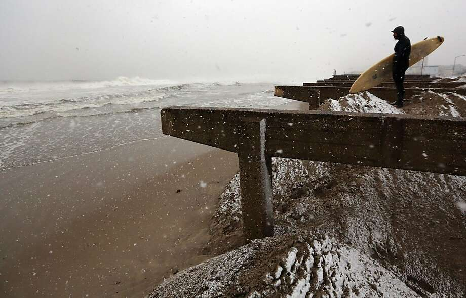 Mandog the surfer watches the waves on Rockaway Beach from atop sand packed to prevent a surge as a storm blows in. Photo: Mario Tama, Getty Images