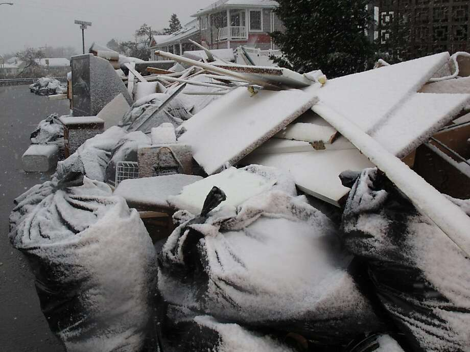 Snow covers debris piles as flood waters start to return to neighborhoods in Point Pleasant Beach, N.J.,  Wednesday Nov. 7, 2012, as a nor'easter hits. The storm was threatening new damage to areas of the Jersey shore already devastated last week by Superstorm Sandy. (AP Photo/Wayne Parry) Photo: Wayne Parry, Associated Press