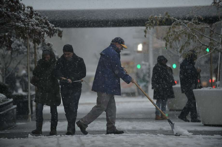 A man shovels snow from a sidewalk on Fifth Avenue as a strong winter storm hits the northeast November 7, 2012 in New York. Photo: Stan Honda, AFP/Getty Images