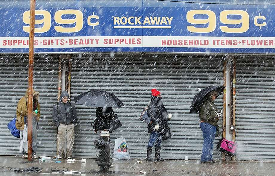 People wait in the snow for a bus while a NorEaster approaches in the Rockaway neighborhood on November 7, 2012 in the Queens borough of New York City. The Rockaway Peninsula was especially hard hit by Superstorm Sandy and some are evacuating ahead to the coming storm. Photo: Mario Tama, Getty Images