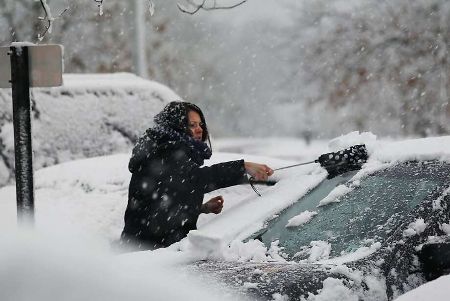 A woman clears snow from her parked car Wednesday, Nov. 7, 2012, in Dover Township, N.J., as the region pounded by Superstorm Sandy last week is hit by a Nor'Easter.  Gov. Chris Christie warned Wednesday that New Jersey may suffer a setback in its Superstorm Sandy recovery efforts as a result of the new storm. Photo: Mel Evans, Associated Press