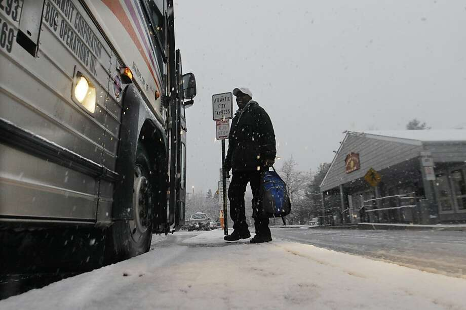As a steady snow falls, a commuter boards a bus for Atlantic City Wednesday, Nov. 7, 2012, in Dover Township, N.J., as the region pounded by Superstorm Sandy last week is hit by a Nor'Easter.  Gov. Chris Christie warned Wednesday that New Jersey may suffer a setback in its Superstorm Sandy recovery efforts as a result of the new storm.  Photo: Mel Evans, Associated Press