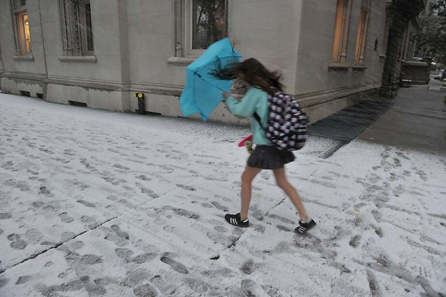 A girl struggles with an unbrella in the wind and snow on Park Avenue as a strong winter storm hits the northeast November 7, 2012 in New York. Photo: Stan Honda, AFP/Getty Images