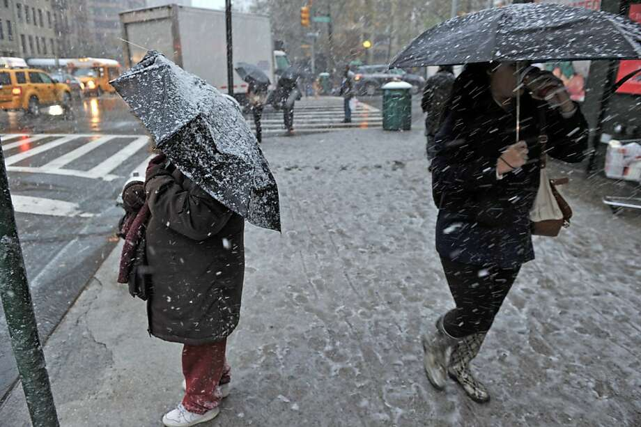 Snow falls as a woman (left) waits for a bus on the corner of East 96th Street and Lexington Avenue as a strong winter storm hits the northeast November 7, 2012 in New York. Photo: Stan Honda, AFP/Getty Images