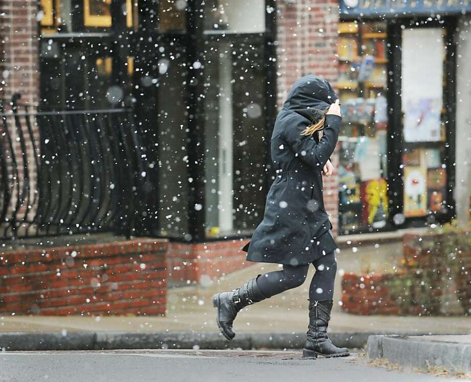 A woman walks on Greenwich Avenue in the snow during the nor'easter that hit town, Wednesday, November 7, 2012. Photo: Bob Luckey