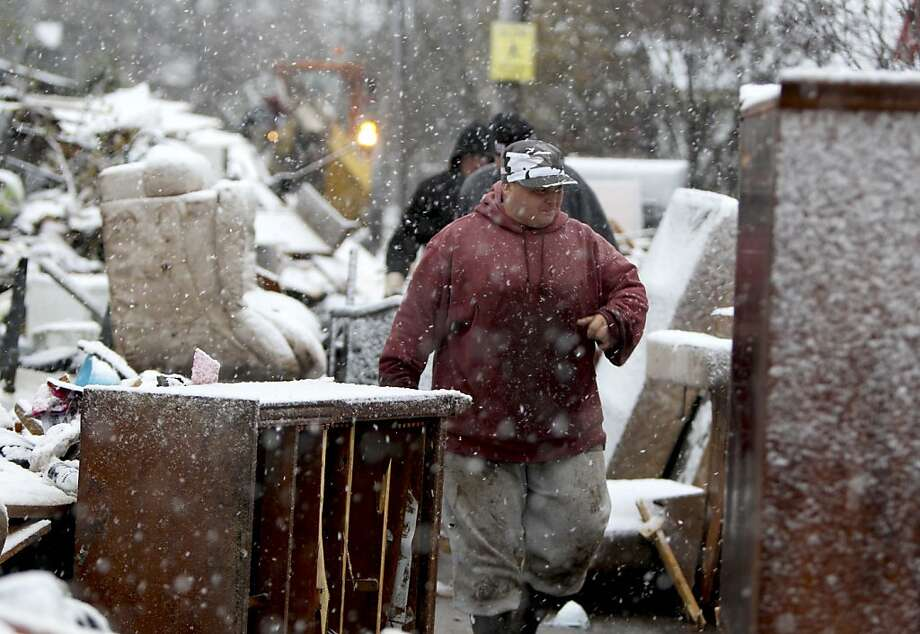 John Barbaria walks in the snow, among piles of trash in the street, while cleaning a relatives house in the New Dorp section of Staten Island, New York, Wednesday, Nov. 7, 2012. Photo: Seth Wenig, Associated Press