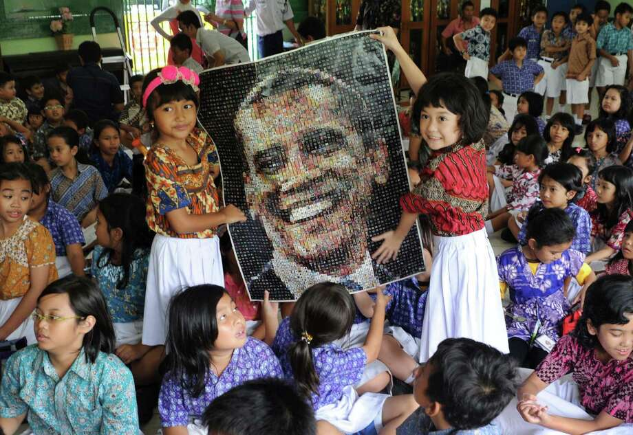 Students hold a poster of U.S. President Barack Obama as they watch the US election vote counting at SDN 01 Menteng elementary school where Obama studied in Jakarta, Indonesia, Wednesday, Nov. 7, 2012. Obama attended the school when he was a child while living in the Southeast Asian nation. Photo: Associated Press / AP
