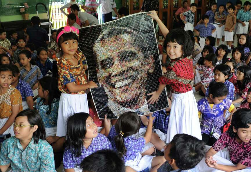 Students hold a poster of U.S. President Barack Obama as they watch the US election vote counting at