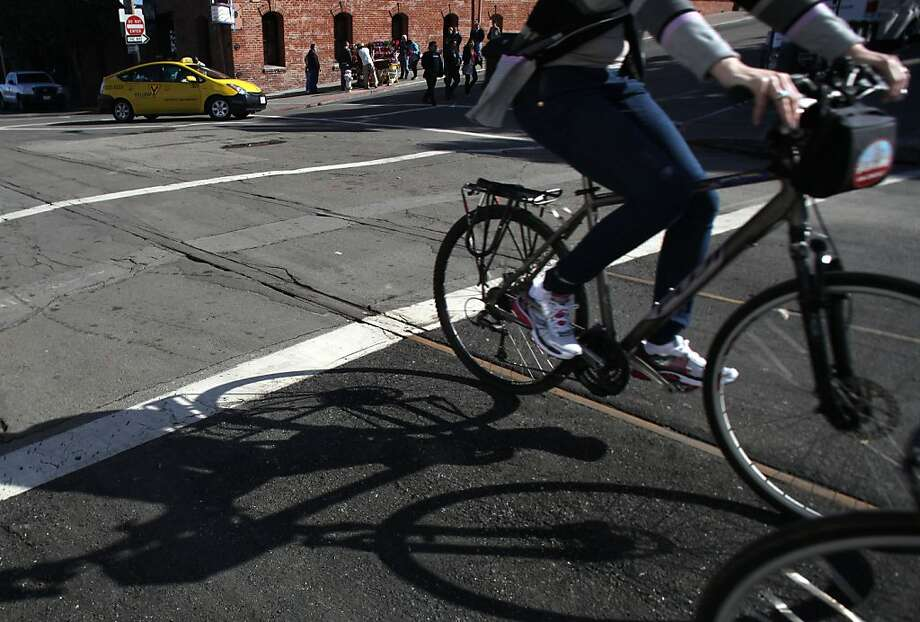 Cyclists pass the partly hidden railroad tracks at Jefferson and Hyde streets. The aban- doned tracks are a booby trap for bicycle wheels. Photo: Liz Hafalia, The Chronicle
