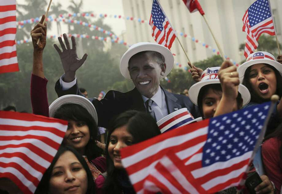 Indian students react in front of photographers next to a cardboard cutout of President Barack Obama after he was projected as the winner during an event organized by the U.S embassy at the landmark Imperial Hotel in New Delhi, India, Wednesday, Nov. 7, 2012. Obama captured a second White House term, blunting a mighty challenge by Republican Mitt Romney as Americans voted for a leader they knew over a wealthy businessman they did not. Photo: Kevin Frayer, Associated Press / AP