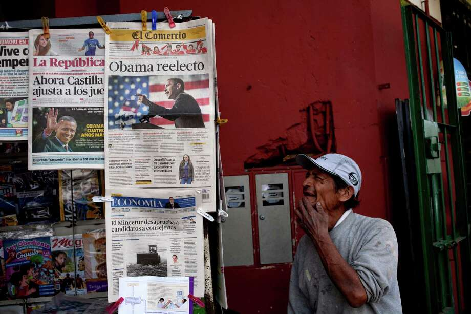 A man looks at newspapers attached to a stand displaying front pages featuring pictures of U.S. President Barack Obama, in Lima, Peru, Wednesday, Nov. 7, 2012. Newspapers across the globe featured photos of Obama who was re-elected for a second presidential term, defeating his Republican challenger, former Massachusetts Gov. Mitt Romney in Tuesday's election. Photo: Rodrigo Abd, Associated Press / AP