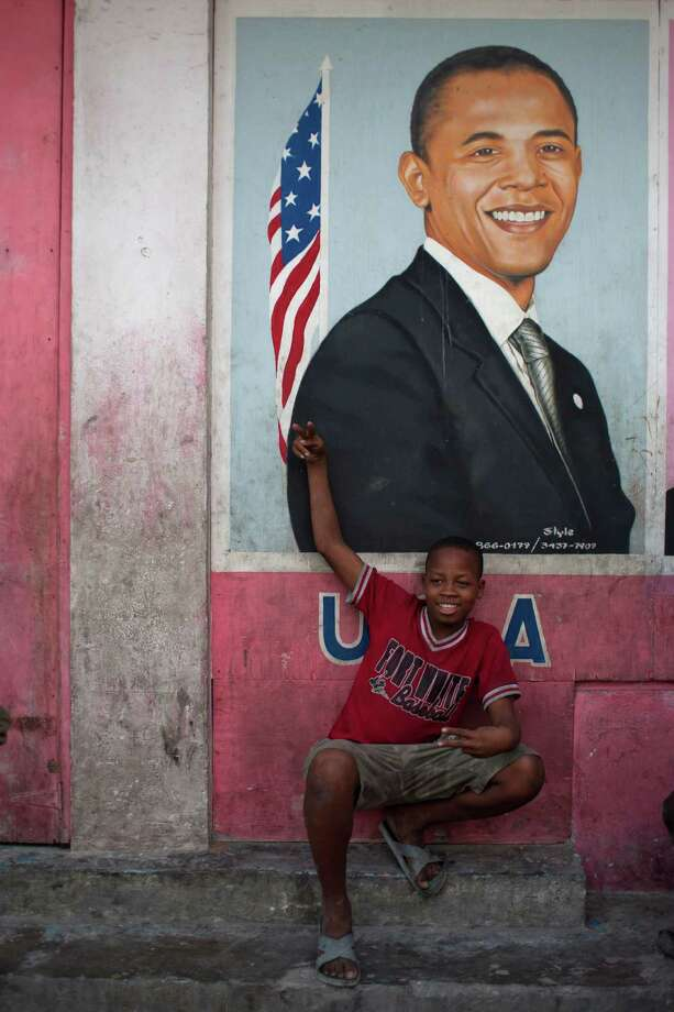 Resident Thony Jeff, 14, poses for pictures in front of an image depicting President Barack Obama in Petion-Ville, Haiti, Wednesday Nov. 7, 2012. Obama was re-elected for a second presidential term, defeating his Republican challenger, former Massachusetts Gov. Mitt Romney in Tuesday's election. Photo: Dieu Nalio Chery, Associated Press / AP