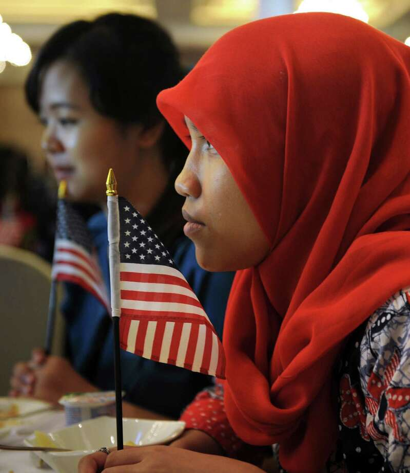 Indonesian student of international relations Anisa Widya Lestari, (C), 20, holds a US flag as visitors watch US presidential elections at the poll monitoring center set up by the US embassy in Jakarta on November 7, 2012. Surveys indicate Indonesia the world's most populous Muslim country favors President Barack Obama who spent four years of his childhood in Jakarta over Republican rival Mitt Romney. Photo: ROMEO GACAD, AFP/Getty Images / AFP