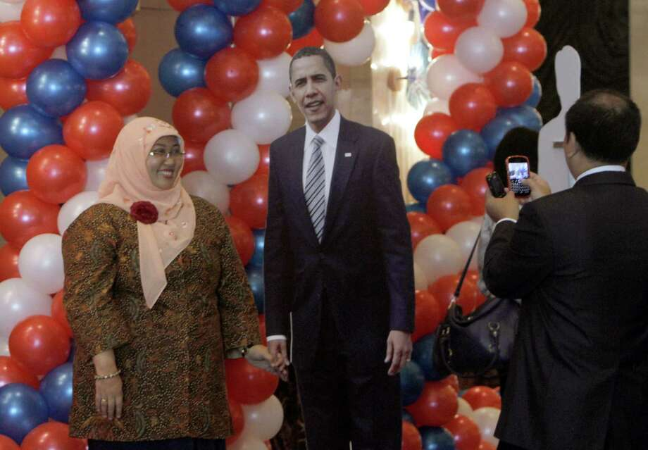 A Muslim woman poses for a photo with a cutout of President Barack Obama during a victory celebration for Obama in the U.S. presidential election in an event hosted by the U.S. Embassy in Jakarta, Indonesia, Wednesday, Nov. 7, 2012. Photo: Tatan Syuflana, Associated Press / AP