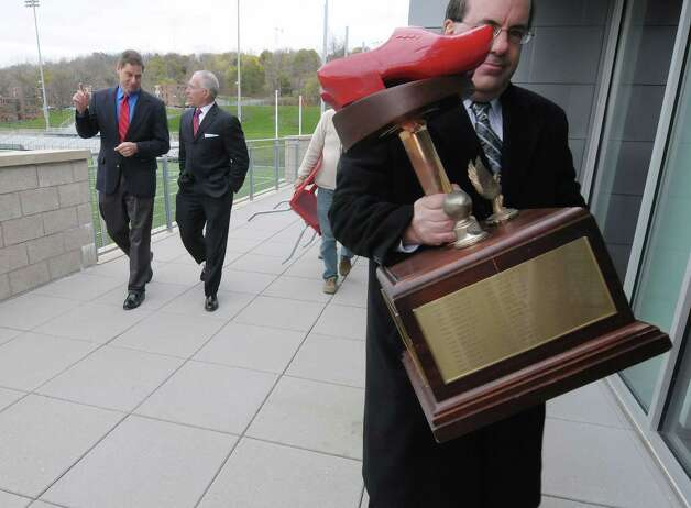 Eric McDowell, foreground, assistant athletic director, sports information for Union College, carries the Dutchman Shoes trophy after it was used in a photograph with Bob Bodor, far left, RPI head football coach, and John Audino, second from left,  Union head football coach at the East Campus Athletic Village at RPI on Wednesday, Nov. 7, 2012 in Troy, NY.  RPI and Union football will meet on Saturday for the 112th Dutchman Shoes football game.  (Paul Buckowski / Times Union) Photo: Paul Buckowski  / 00019960A