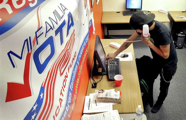 Pedro Yazzie, 27, makes phone calls Tuesday, Nov. 6, 2012 in Phoenix to registered voters from the offices of Mi Familia Vota, a non-partisan effort to increase voter participation among Latinos and others. (AP Photo/Matt York) Photo: Matt York, Associated Press / AP