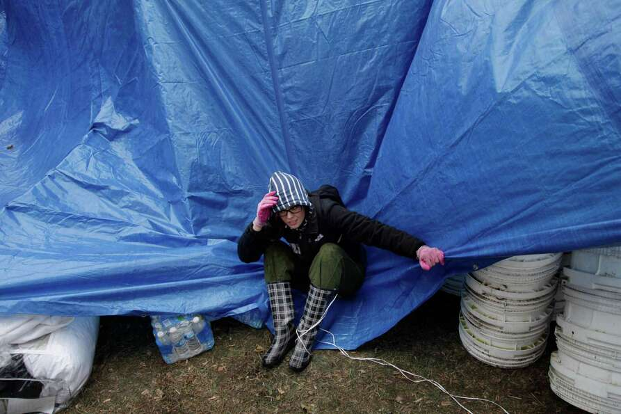 Gina Kohm tries to keep a tarp from blowing away which covers a pile of donated supplies at an aid s