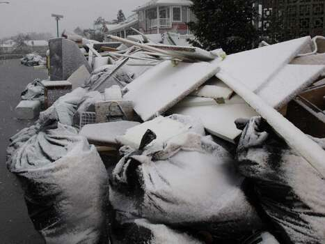 Snow covers debris piles as flood waters start to return to neighborhoods in Point Pleasant Beach, N.J.,  Wednesday Nov. 7, 2012, as a nor'easter hits. The storm was threatening new damage to areas of the Jersey shore already devastated last week by Superstorm Sandy. Photo: Wayne Parry, Associated Press / AP