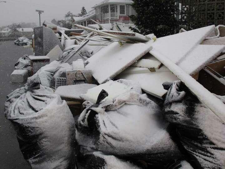 Snow covers debris piles as flood waters start to return to neighborhoods in Point Pleasant Beach, N